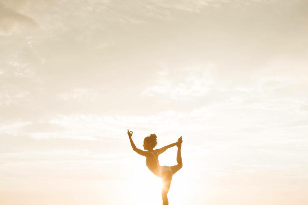 Frau macht eine Yogaübung, Sonnenuntergang im Hinterrund